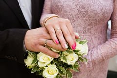Hands with wedding rings and flower bouquet Royalty Free Stock Images