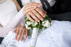 Hands with wedding rings over the bouquet Royalty Free Stock Image