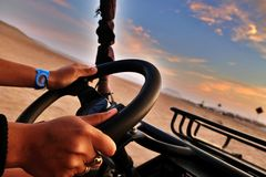Hands on the wheel. Crossing the desert in a buggy royalty free stock image