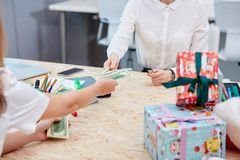 Hands transfer money to other hands on the background of a table with gifts. Hands in which a bundle of dollars transfer money to other hands in the background stock photos