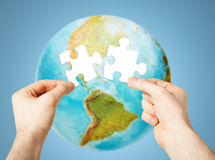 Hands with white blank puzzle over earth globe Royalty Free Stock Photography