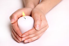 Hands and white candle. Over white Stock Photography