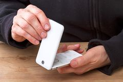 Hands with a white cell phone Stock Images