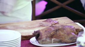 Hands in white gloves cut meat by big knife on wooden kitchen board. Close up. stock footage