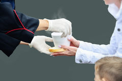 Hands in white gloves give a cup of hot soup to a woman with child. Royalty Free Stock Photos