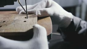 Cutting jigsaw in a wooden workpiece, the symbol of bitcoin. Hands in white gloves jigsaw to cut a wooden workpiece, the symbol of bitcoin stock video footage