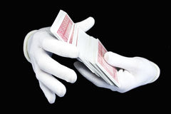 Hands in white gloves with a pack of playing cards. On a black background Stock Photo