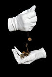 Hands in white gloves pour fine coins Stock Images