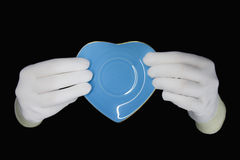 Hands in white gloves with saucer form of heart