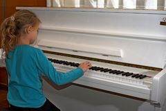 Hands on the white Keys of the Piano Playing a Melody. Women`s Hands on the Keyboard of the Piano, Playing the Notes Melody. Hand. S of young Girl, Music on the stock images