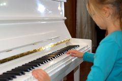 Hands on the white Keys of the Piano Playing a Melody. Women`s Hands on the Keyboard of the Piano, Playing the Notes Melody. Hand. S of young Girl, Music on the royalty free stock image
