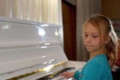 Hands on the white Keys of the Piano Playing a Melody. Women`s Hands on the Keyboard of the Piano, Playing the Notes Melody. Hand. S of young Girl, Music on the royalty free stock photography