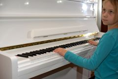 Hands on the white Keys of the Piano Playing a Melody. Women`s Hands on the Keyboard of the Piano, Playing the Notes Melody. Hand. S of young Girl, Music on the stock photo