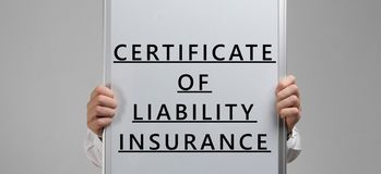 Men`s hands holding a poster with the inscription certificate of liability insurance isolated on light background. Hands in a white shirt hold a banner about stock images