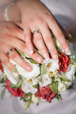 Hands whith rings on wedding bouquet Royalty Free Stock Images