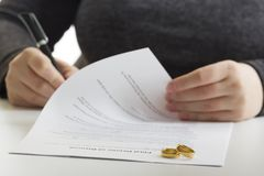 Hands of wife, husband signing decree of divorce, dissolution, canceling marriage, legal separation documents, filing. Divorce papers or premarital agreement Royalty Free Stock Photos