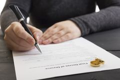 Hands of wife, husband signing decree of divorce, dissolution, canceling marriage, legal separation documents, filing. Divorce papers or premarital agreement Royalty Free Stock Photography