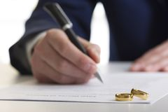 Hands of wife, husband signing decree of divorce, dissolution, canceling marriage, legal separation documents, filing. Divorce papers or premarital agreement Stock Photos