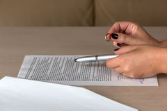 Hands of wife signing divorce documents, returning wedding ring Royalty Free Stock Photography