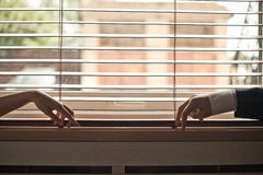Hands on a window sill. Royalty Free Stock Photo