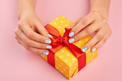 Hands with winter manicure unpacking present. Close up of female hands with beautiful manicure is opening gift box with red ribbon. Holiday and celebration Royalty Free Stock Photography