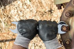 Free Hands With Work Gloves Holding A Wrench And Tighten Very Rusty Bolts Royalty Free Stock Images - 77803749