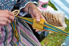 The hands of the wizard, who weaves a colorful hair ribbon. Closeup. Folk art of Russia. Closeup stock images