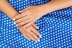 Hands of woman with art manicure on cloth. Female hands on white blue polka dots background. Stylish beautiful manicure. Nails car royalty free stock photos