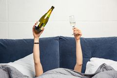 Hands of woman with bottle and glass of champagne in bed stock image
