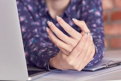 Hands of woman with carpal tunnel syndrome over computer keyboard close-up. Close-up image of woman hands with carpal tunnel syndrome over computer keyboard royalty free stock photos