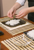 Hands of woman chef filling japanese sushi rolls Royalty Free Stock Photography