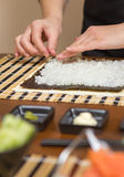 Hands of woman chef filling japanese sushi rolls Stock Photos