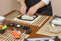 Hands of woman chef filling japanese sushi rolls Stock Images