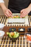 Hands of woman chef rolling up a japanese sushi Stock Images