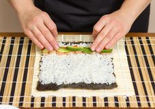 Hands of woman chef rolling up a japanese sushi Stock Image