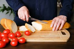 Hands of a woman or a cook cut with a knife a loaf of bread, a loaf or a baguette into slices on a wooden cutting Board. Near ripe royalty free stock image