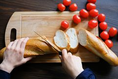 Hands of a woman or a cook cut with a knife a loaf of bread, a loaf or a baguette into slices on a wooden cutting Board. Near ripe stock image