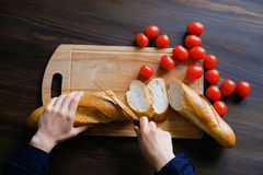 Hands of a woman or a cook cut with a knife a loaf of bread, a loaf or a baguette into slices on a wooden cutting Board. Near ripe royalty free stock photo