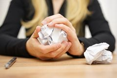 Hands of woman crumple sheets of paper at the table Royalty Free Stock Photo
