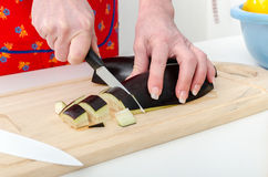 Hands of woman cutting eggplant Royalty Free Stock Images