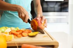 Hands of a woman cutting some vegetables and fruits in wooden table in the kitchen. Close-up of hands of a woman cutting some vegetables and fruits in wooden royalty free stock photography