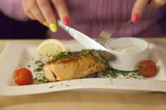 Hands of the woman cutting stake from fish a plate Royalty Free Stock Image