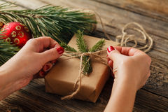 Hands of woman decorating Christmas gift box Royalty Free Stock Images