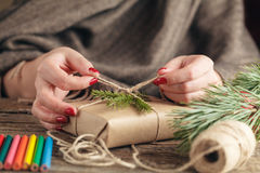 Hands of woman decorating Christmas gift box Stock Photos
