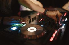 Hands of woman DJ tweak various track controls on dj`s deck at night club Stock Photography
