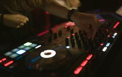 Hands of woman DJ tweak various track controls on dj`s deck at night club Royalty Free Stock Photos