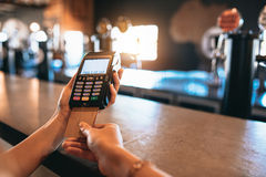 Hands of woman doing cashless payment at bar. Hands of woman paying bill using a credit card at bar. Cropped shot of female at brewery factory doing cashless Stock Photography