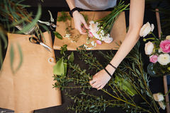 Hands of woman florist creating flower bouquet on table Royalty Free Stock Photos