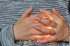 The hands of the woman are folded in the region of the heart through which the light passes. Theme of love, feelings. Emotions. Close-up royalty free stock images