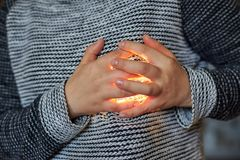 The hands of the woman are folded in the region of the heart through which the light passes. Theme of love, feelings. Emotions. Close-up royalty free stock image